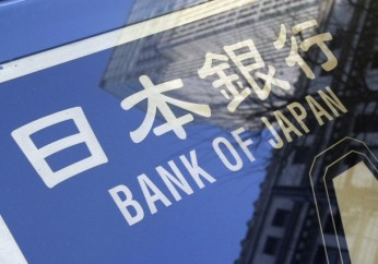 Buildings are reflected on a Bank of Japan board in Tokyo